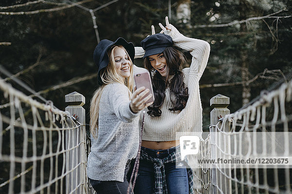 Zwei glückliche junge Frauen auf einer Hängebrücke  die einen Selfie nehmen.