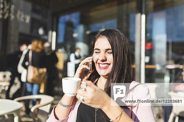 Lachende junge Geschäftsfrau am Handy in einem Outdoor-Café