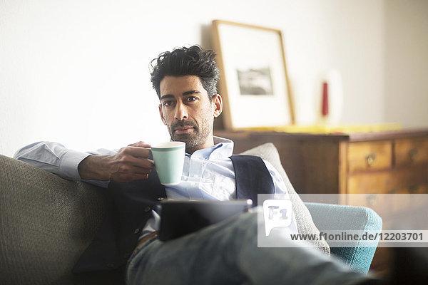 Porträt eines nachdenklichen Mannes mit Kaffeetasse und Tablette auf dem Sofa zu Hause