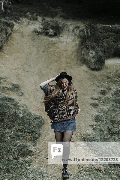 Modische junge Frau mit Hut und Poncho  die bergab läuft.