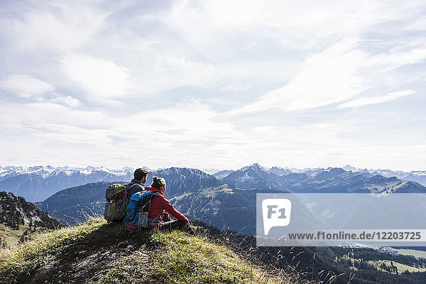 Austria  Tyrol  young couple sitting in mountainscape looking at view
