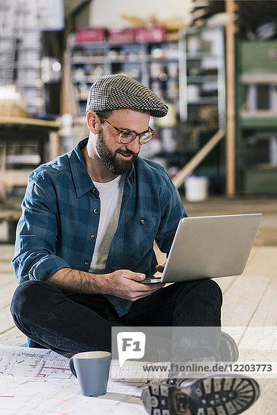 Lächelnder Mann mit Laptop und Bauplan auf dem Boden sitzend
