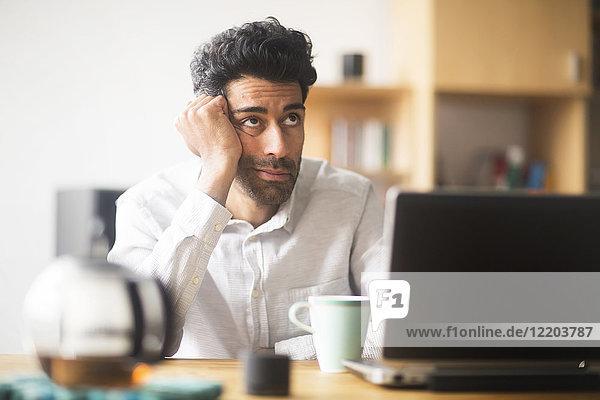 Porträt eines denkenden Geschäftsmannes am Schreibtisch in seinem Büro