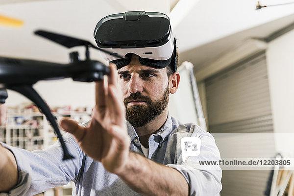 Mann mit VR-Brille hält Drohne
