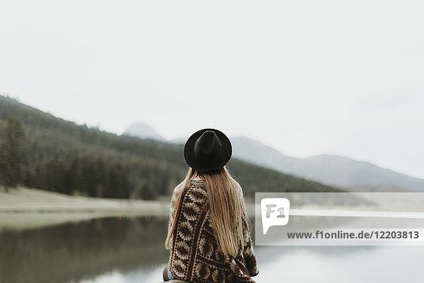 Rückansicht der jungen Frau mit Hut und Poncho vor dem See