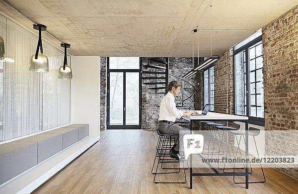 Geschäftsmann mit Laptop im modernen Büro