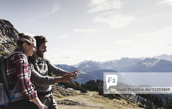 Österreich  Tirol  lächelndes junges Paar  das sich in der Bergwelt vergnügt.