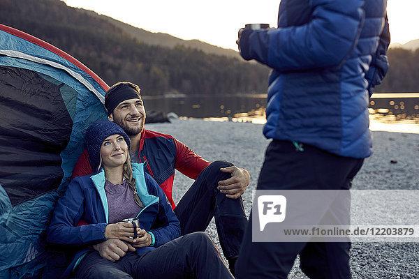 Lächelndes junges Paar mit Freund im Zelt am Seeufer