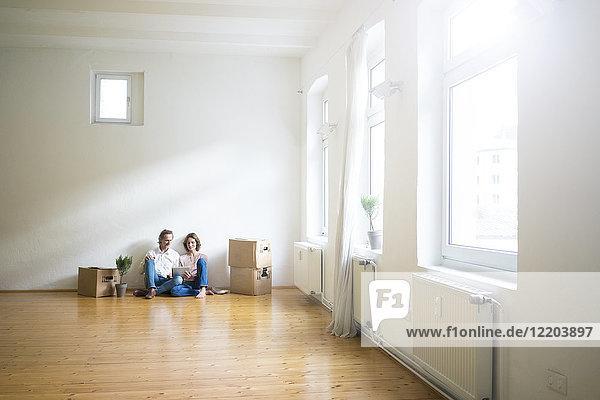 Das reife Paar sitzt auf dem Boden in einem leeren Raum neben den Kartons mit Tabletten.