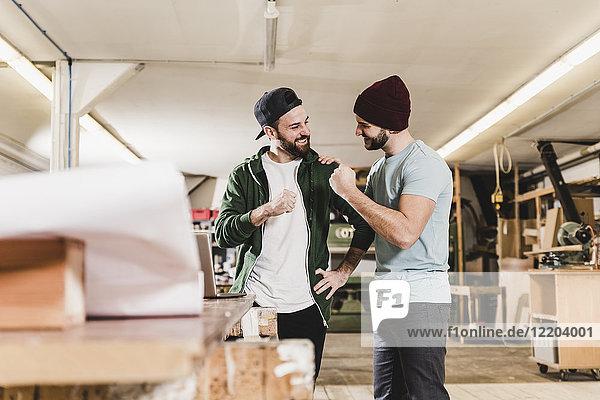 Zwei glückliche junge Männer mit Laptop in der Werkstatt
