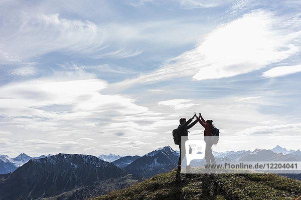 Österreich  Tirol  junges Paar  das in der Berglandschaft steht und jubelt