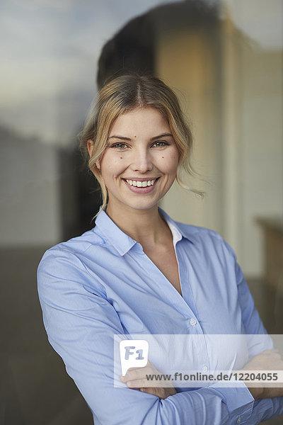Portrait der Content-Geschäftsfrau hinter der Fensterscheibe
