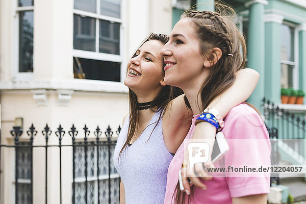 Two happy teenage girls on the go in the city
