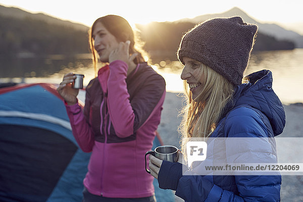 Two female friends at tent holding mugs