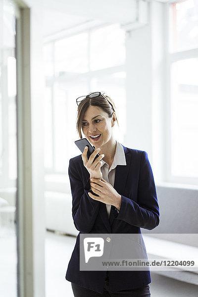 Geschäftsfrau mit Handy im hellen Zimmer