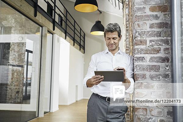 Portrait eines reifen Geschäftsmannes mit Tablette im modernen Büro