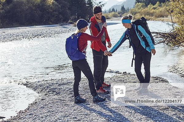 Freundeskreis beim Händeschütteln am Flussufer