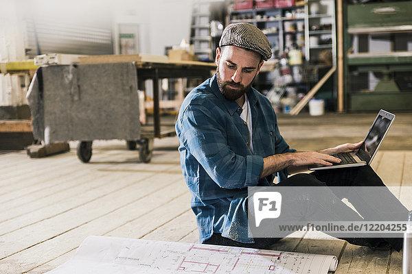 Mann mit Laptop auf dem Boden sitzend mit Blick auf den Bauplan