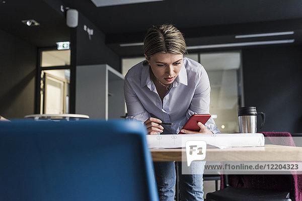 Junge Frau mit Handy und Plan am Tisch im Büro