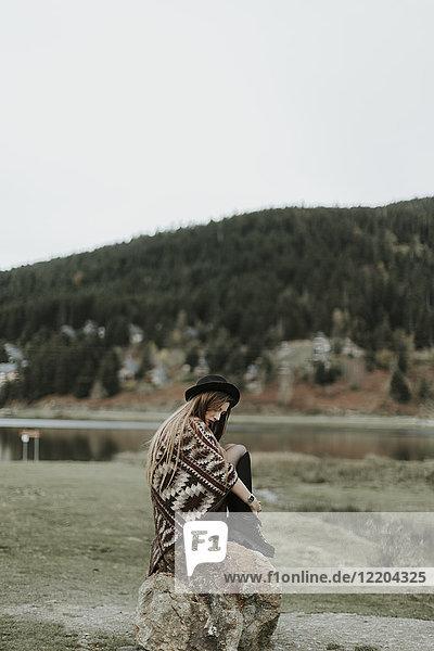 Modische junge Frau mit Hut und Poncho auf einem Felsen sitzend