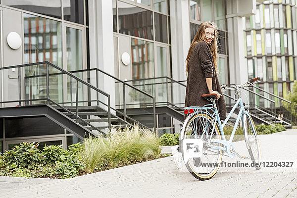 Porträt einer lächelnden Frau mit Fahrrad vor einem Gebäude