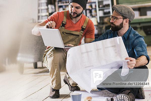 Zwei Männer mit Tablettenblick und Zugluft auf dem Boden sitzend