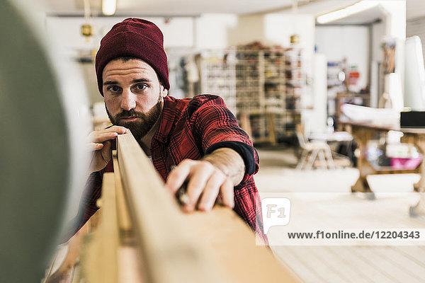 Mann untersucht Holz in der Werkstatt