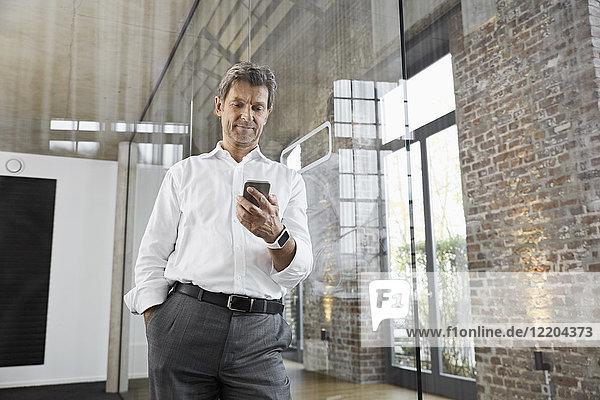 Ausgereifter Geschäftsmann mit Smartphone im modernen Büro