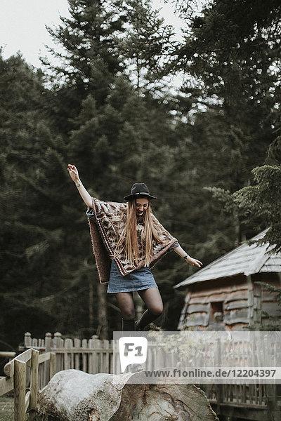 Modische junge Frau mit Hut und Poncho auf dem Baumstamm
