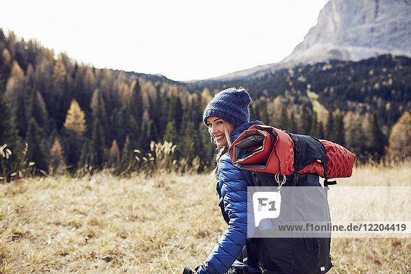 Glückliche junge Frau beim Wandern in den Bergen