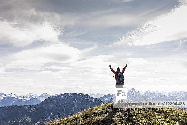 Österreich  Tirol  junge Frau stehend in der Berglandschaft jubelnd