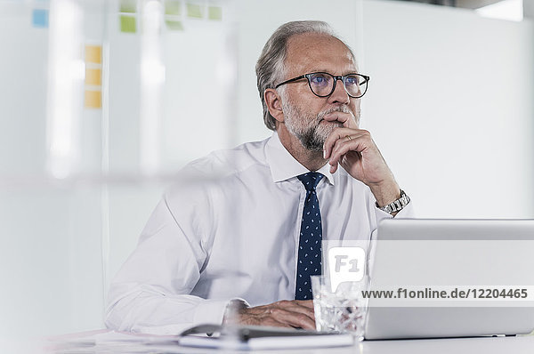 Mature businessman with laptop at desk in office thinking