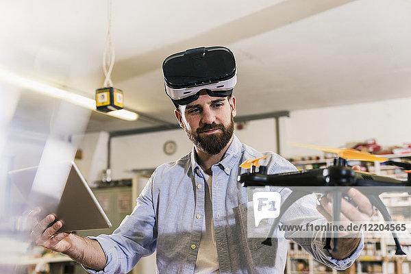Mann mit VR-Brille mit Drohne und Tablette