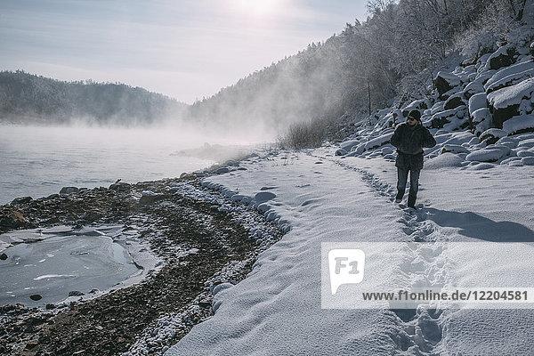 Russland  Oblast Amur  Wanderer am Flussufer von Bureya in verschneiter Natur