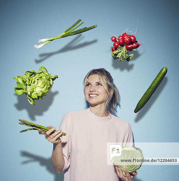 Porträt einer glücklichen jungen Frau  die mit Gemüse jongliert.