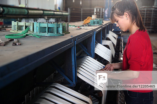 Woman working on silk spinning machine in traditional silk factory  Dalat  Vietnam  Indochina  Southeast Asia  Asia