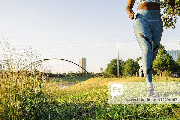 Legs of mixed race woman running in grass near waterfront