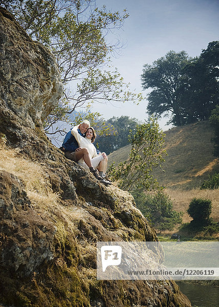 Caucasian couple sitting on hill near river
