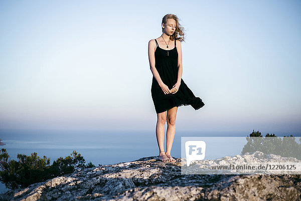 Wind blowing dress of Caucasian woman standing on rock near ocean