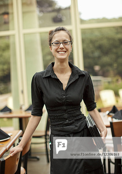 Portrait of smiling Hispanic waitress holding menus in restaurant