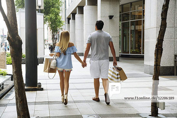 Caucasian couple holding hands carrying shopping bags in city