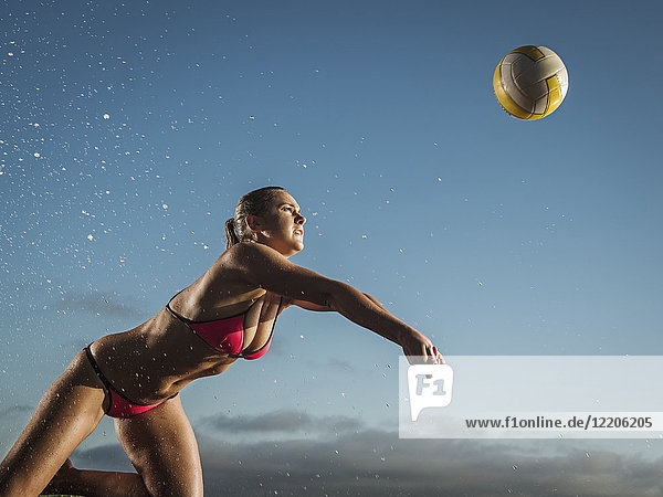Caucasian woman diving to volleyball