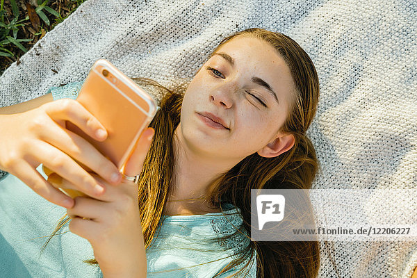 Confused Caucasian girl laying on blanket texting on cell phone