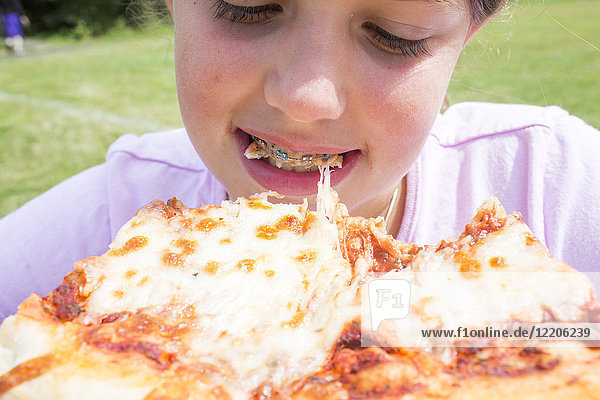 Close up of Caucasian girl with braces biting pizza