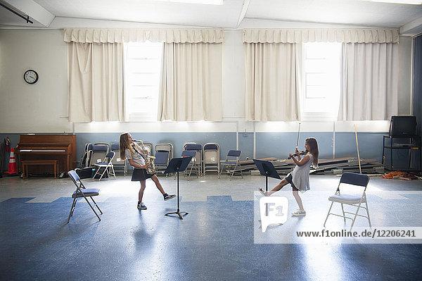 Caucasian girls practicing violins and dancing