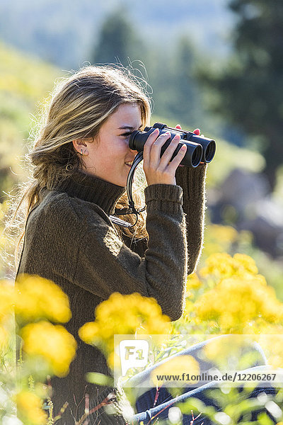 Caucasian girl in field using binoculars
