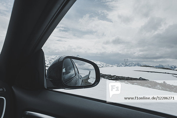 Car side-view mirror near winter landscape