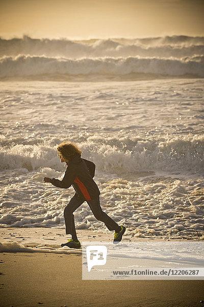 Mixed race boy running on beach