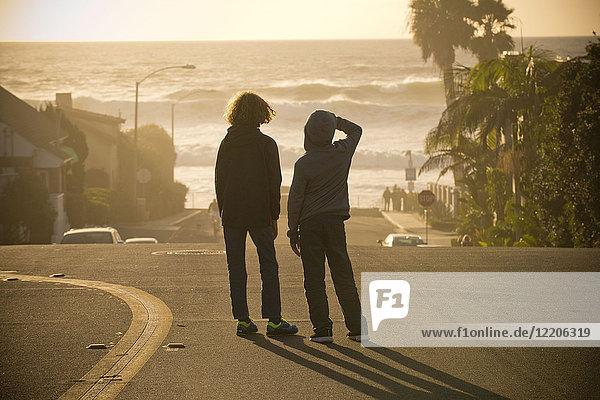 Boys standing in street admiring ocean waves