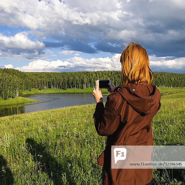 Woman photographing river with cell phone